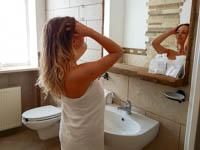 Camera kranabetta ragazza si sistema in bagno di fronte allo specchio