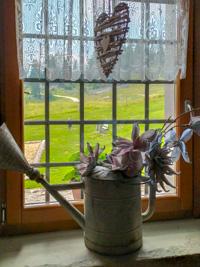 Blumenschmuck und Holzherz am Fenster