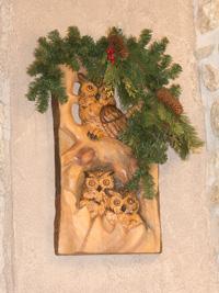 Holzdekoration mit Eulen und Tannenzapfen an der Wand