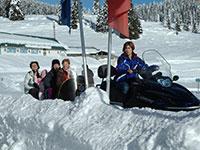 Famiglia in motoslitta con istruttore