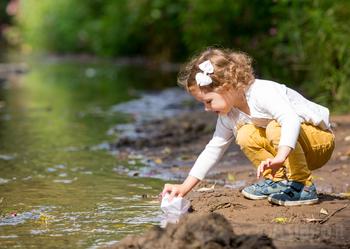 bambina gioca a riva della pozza