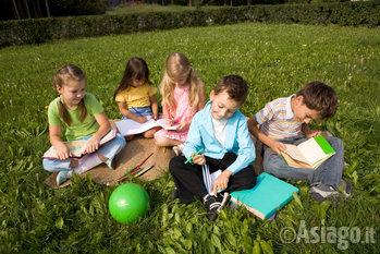 bambini seduti su un prato che disegnano n1