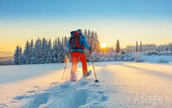 uomo cammina con ciaspole sulla neve al tramonto