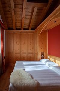 Spaziosa camera matrimoniale con bellissimo soffitto travato e grande armadio in legno, nel lodge n°10