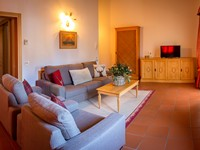 La zona soggiorno dell'appartamento n°10 con grande divano, comode poltrone e tv a schermo piatto