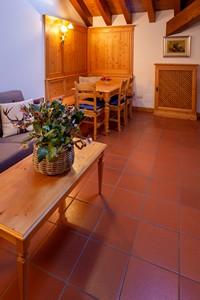 Soggiorno dell'appartamento n°11 con salottino e angolo perlinato in legno con tavolo