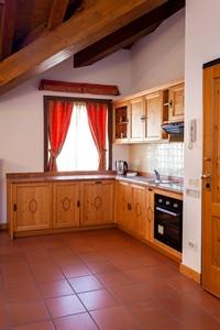 Angolo cottura con cucina accessoriata e ampia finestra nell'appartamento n°2 dell'Asiago Sporting Lodge