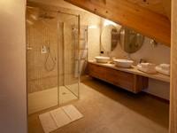L'ampio bagno con doccia della Penthouse, con doppio lavandino e rifiniture di pregio