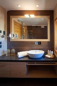 L'angolo con grande specchio e moderno lavandino a ciotola nel bagno della Junior Suite