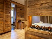 La camera Junior Suite Deluxe avvolge gli ospiti con il calore del legno e del caminetto high tech