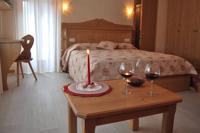 Due bicchieri di buon vino, una candela e si brinda nel salottino della camera Primula