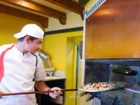 il pizzaiolo della pizzeria la quinta 2002 mentre inforna una delle sue pizze