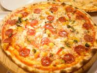pizza con salamino patate al forno zucchine e peperoni grigliati su tagliere